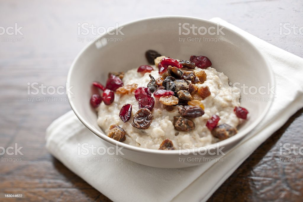 bowl of Porridge oatmeal topped with mixed dried fruit stock photo