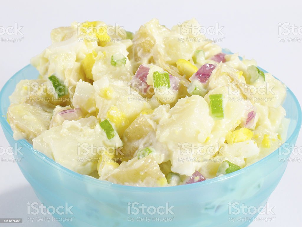 A bowl of potato salad with sliced spring onions and pepper stock photo