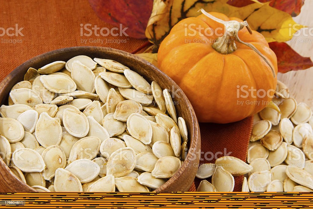 Bowl of pumpkin seeds next to a small pumpkin royalty-free stock photo