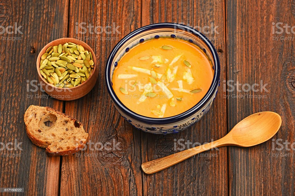 Bowl of pumpkin soup on wooden table royalty-free stock photo