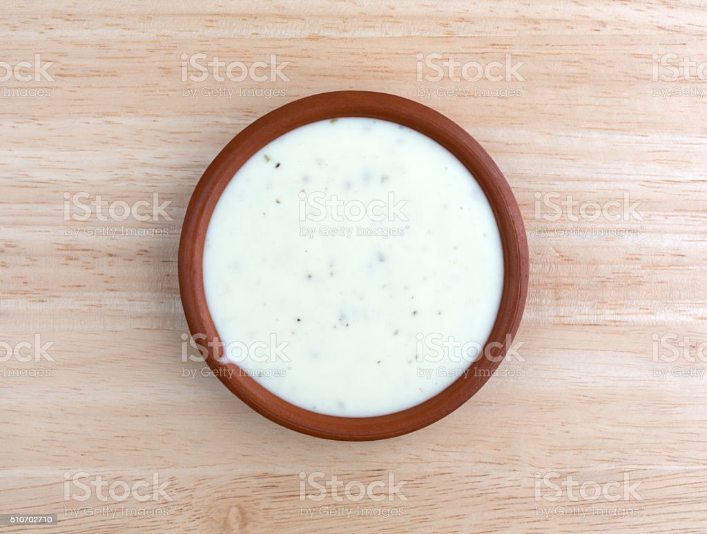 Bowl of ranch dressing on a wood table top view stock photo