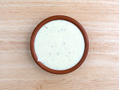 Bowl of ranch dressing on a wood table top view