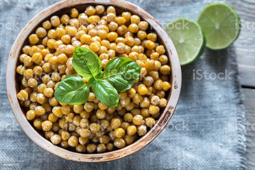 Bowl of roasted chickpeas on the wooden background stock photo