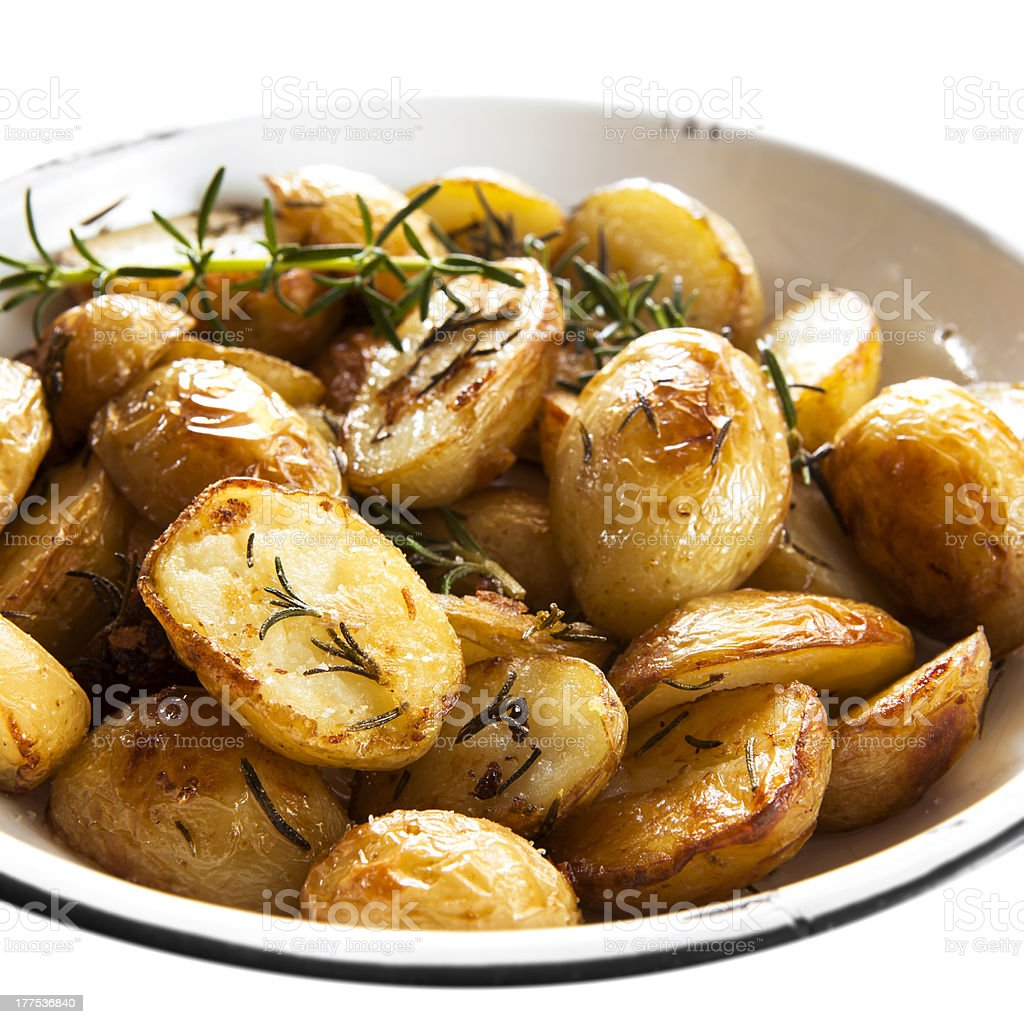 Bowl of roasted potatoes and sprigs of rosemary stock photo