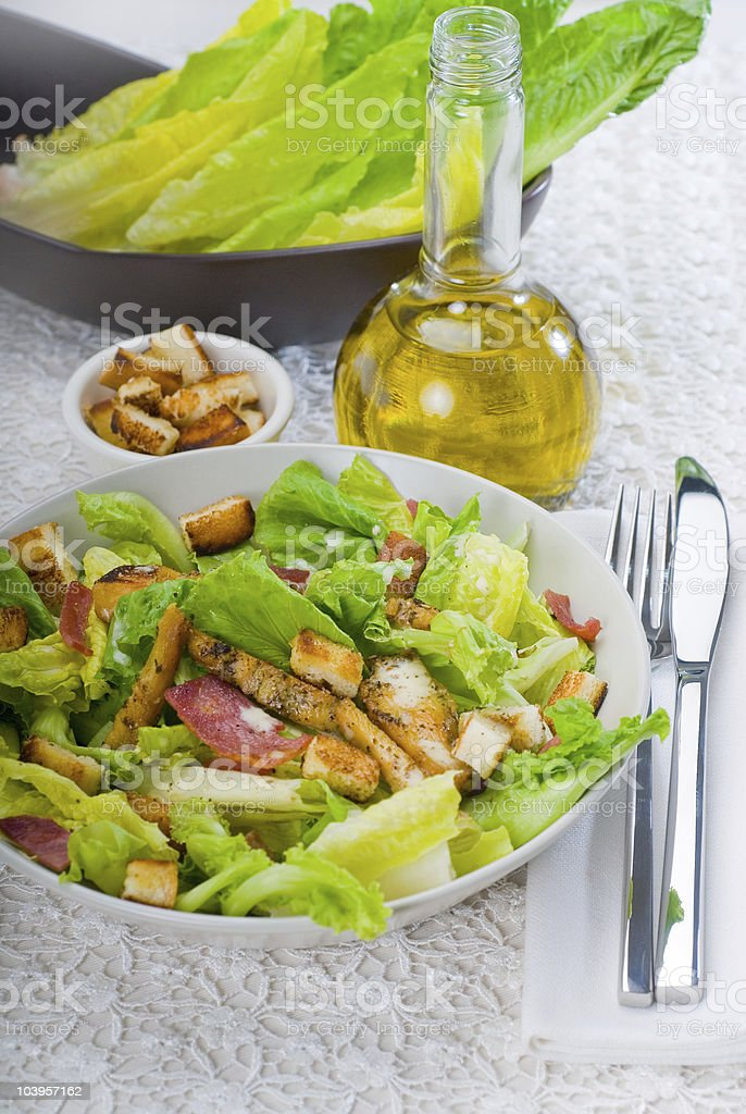 Bowl of salad next to oil bottle and dish royalty-free stock photo