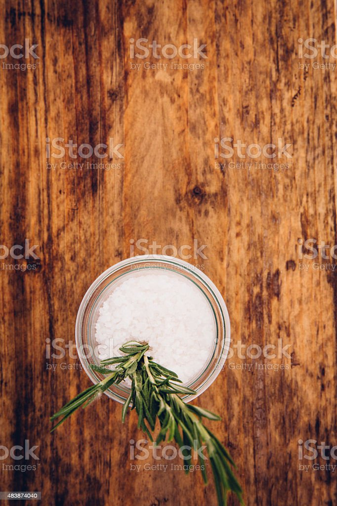 Bowl of salt with sprig of rosemary on vintage wood stock photo