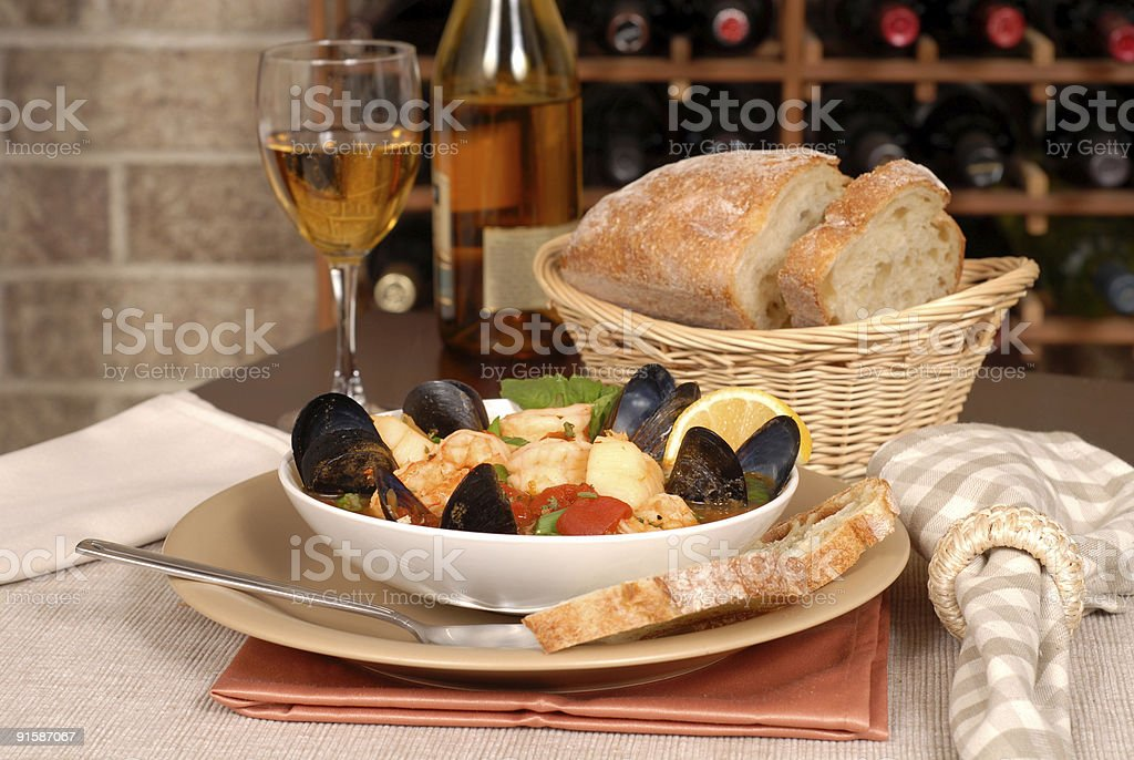 Bowl of seafood soup with wine and rustic bread royalty-free stock photo