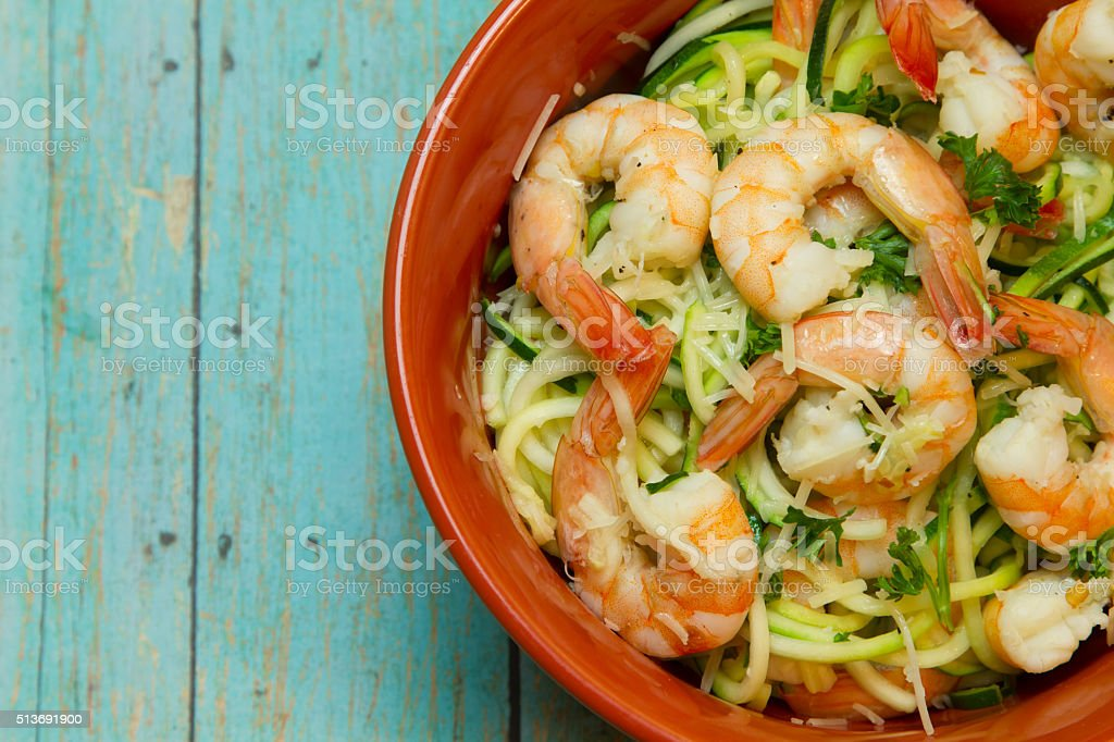 Bowl of Shrimp with Spiralized zucchini on wood board stock photo