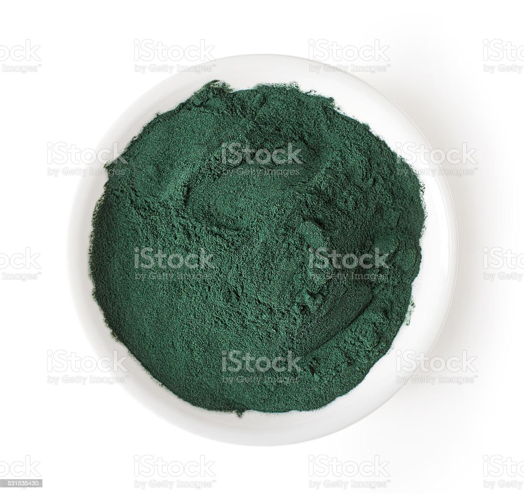 Bowl of spirulina powder isolated on white, from above stock photo