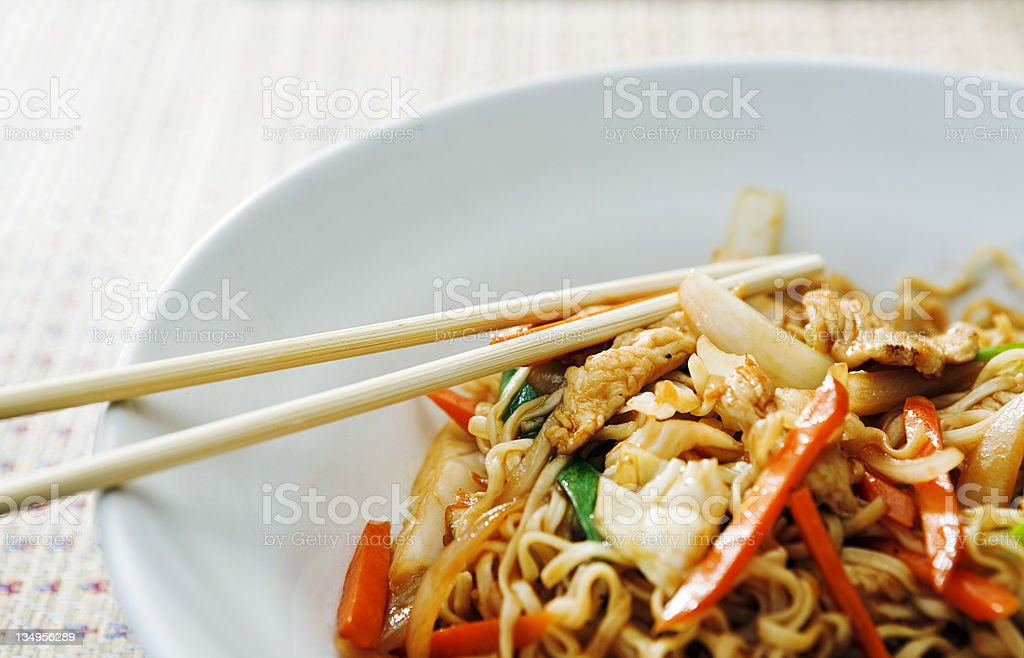 Bowl of Thai stir fried food with noodles and chopsticks stock photo