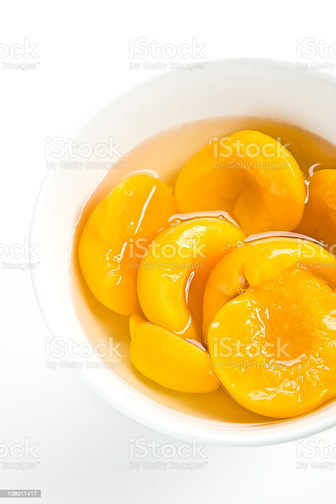 A bowl of tinned peaches on a white background royalty-free stock photo