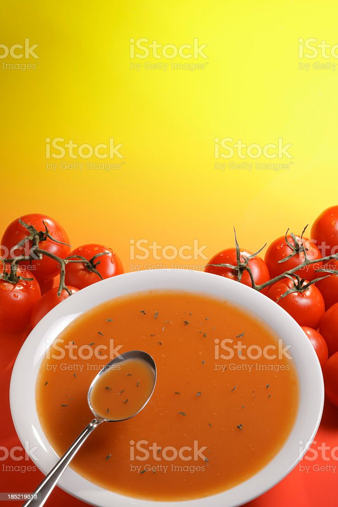 A bowl of tomato cream soup near piles of tomatoes stock photo
