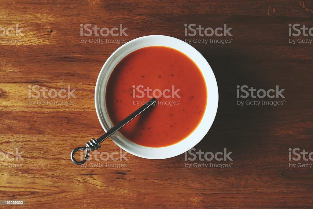 Bowl of Tomato Soup on Oak Table stock photo