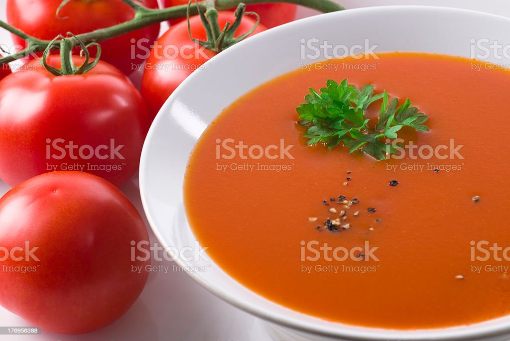 A bowl of tomato soup with tomatoes next to it royalty-free stock photo