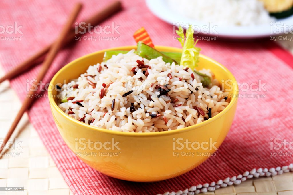 Bowl of various types of rice next to chop sticks royalty-free stock photo