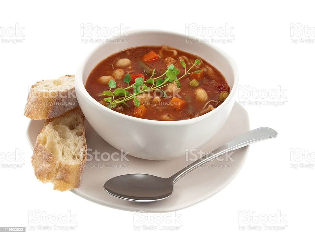 A bowl of vegetable soup with pieces of bread on a saucer stock photo