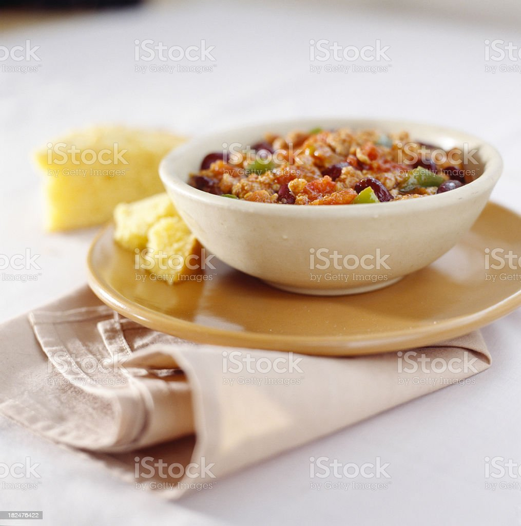 Bowl of vegetable stew with cornbread on plate stock photo