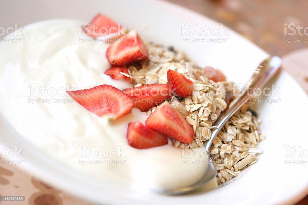 Bowl of yogurt with granola and strawberries royalty-free stock photo
