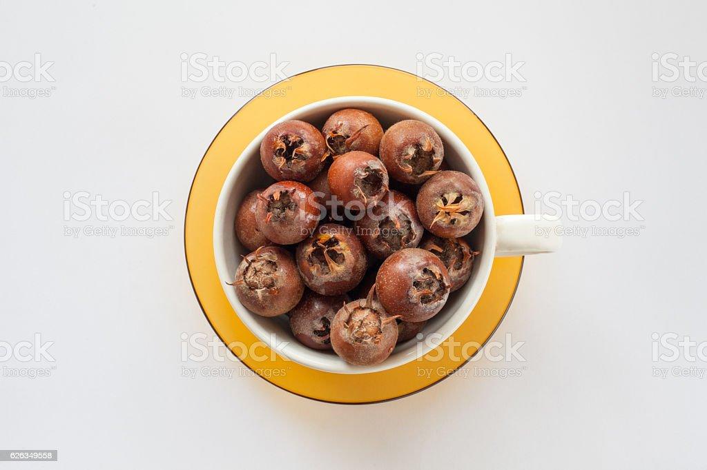 bowl on a yellow saucer full of medlar on white stock photo