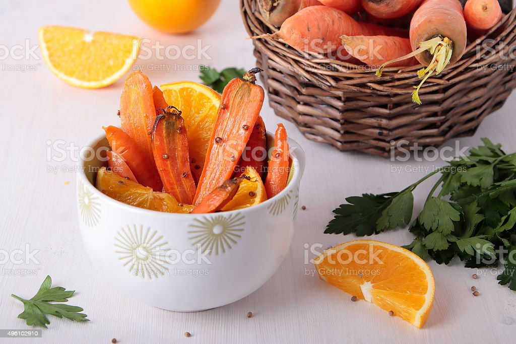 Bowl with baked carrots, coriander and orange stock photo