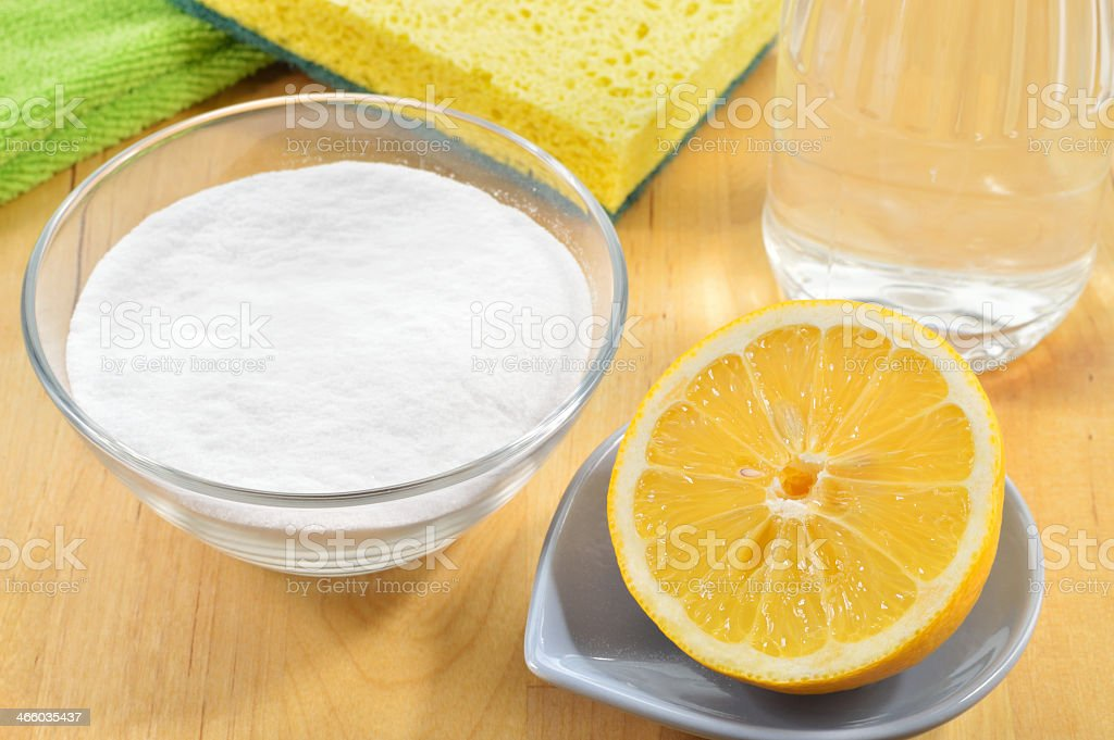 A bowl with baking soda, vinegar, lemon and salt stock photo