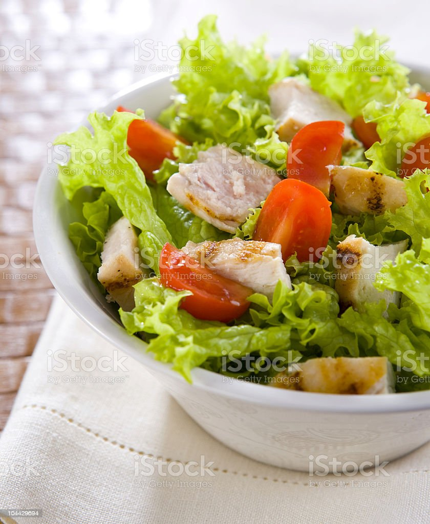 A bowl with chicken and caesar salad stock photo