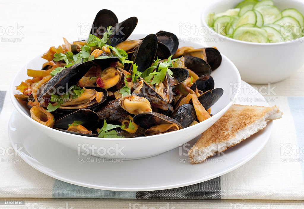 bowl with cooked mussels and cucumber salad stock photo