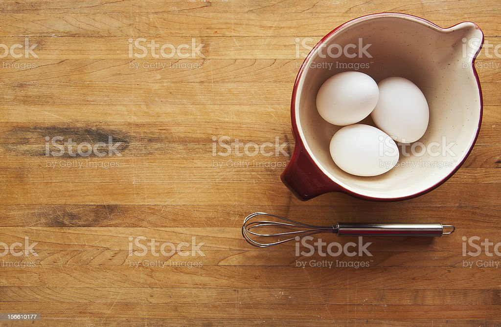 Bowl with eggs and whisk on butcher block counter stock photo