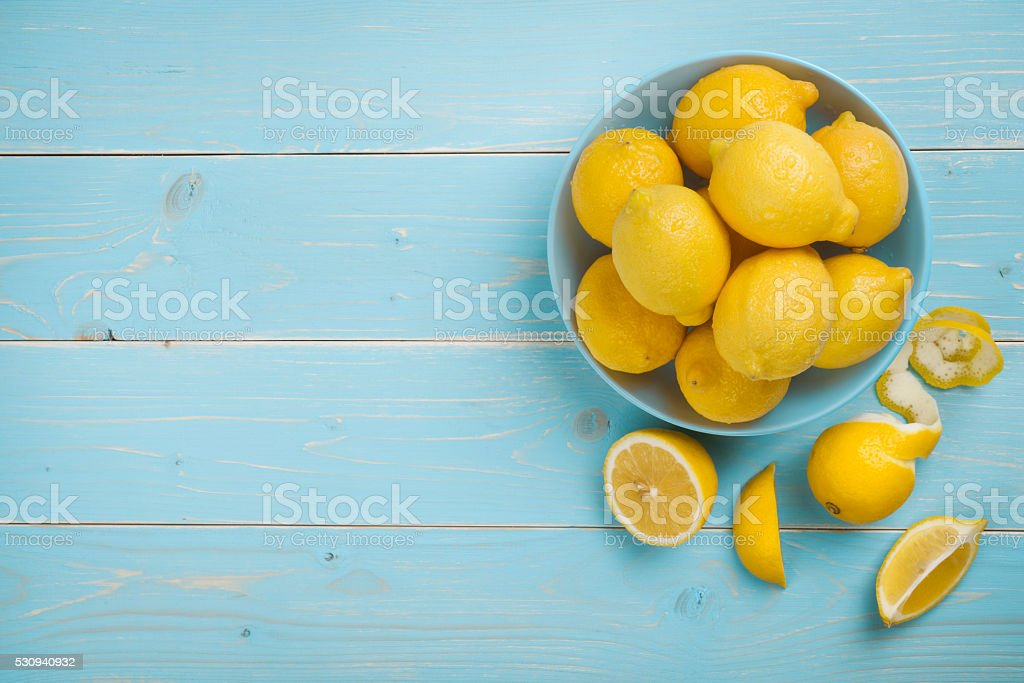 Bowl with fresh lemons on blue wooden background. Top view stock photo