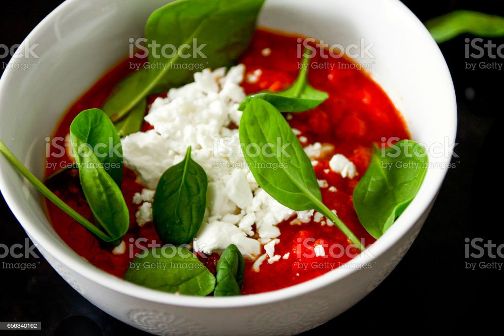 Bowl with fresh tomato soup served with spinach leaves and feta stock photo