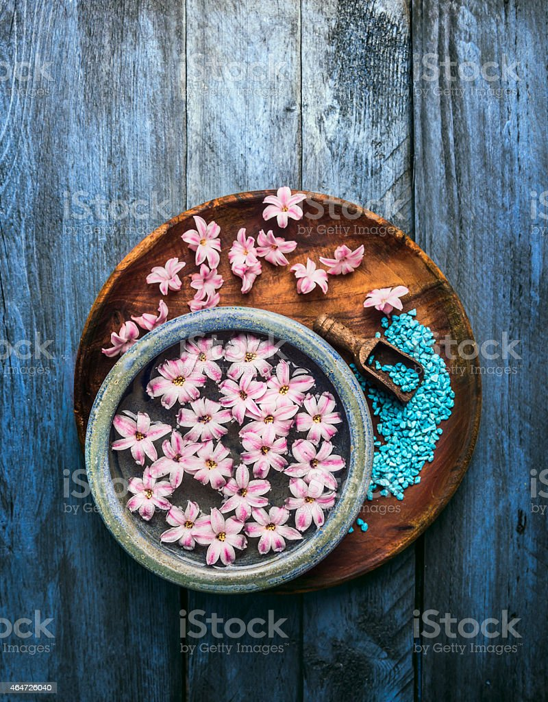 bowl with pink flowers in water,  scoop  of sea salt stock photo