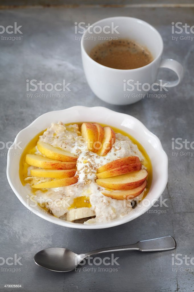 Bowl with porridge, apples, banana, sesame seeds and coffee cup stock photo