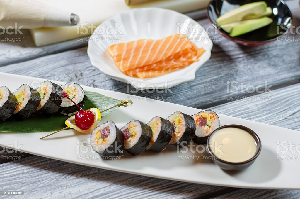 Bowl with sauce beside sushi. stock photo
