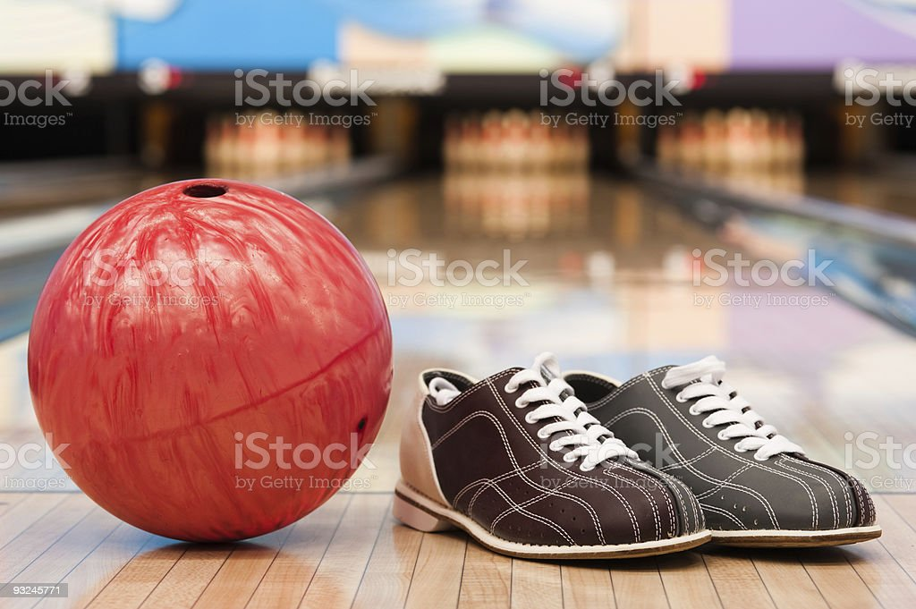 Bowling ball and shoes on lane stock photo