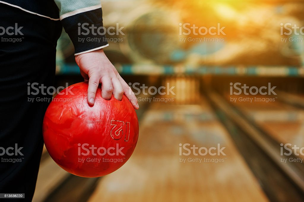 Bowling ball at hand of man background bowling alley stock photo