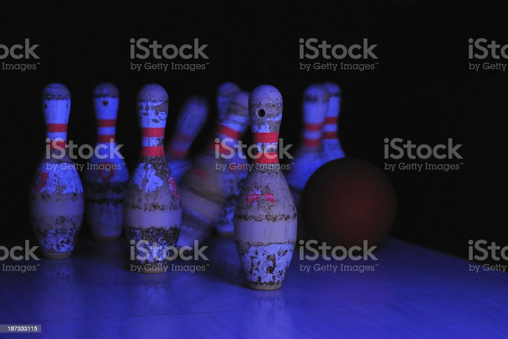 Bowling ball hits tenpins in ultraviolet light stock photo