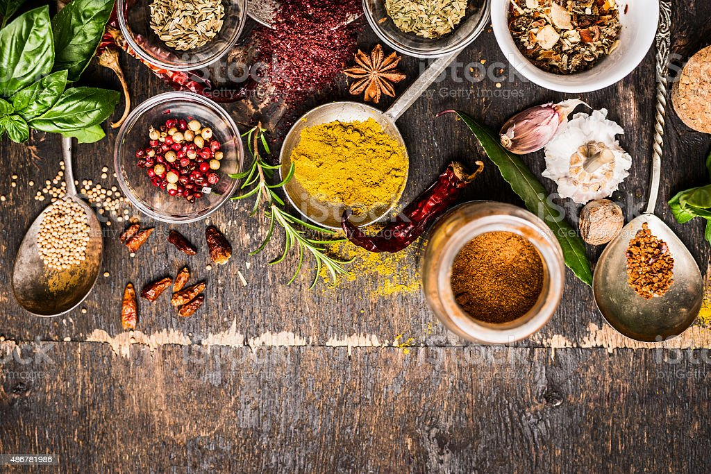 Bowls and spoon of  Various spices selection on rustic background stock photo