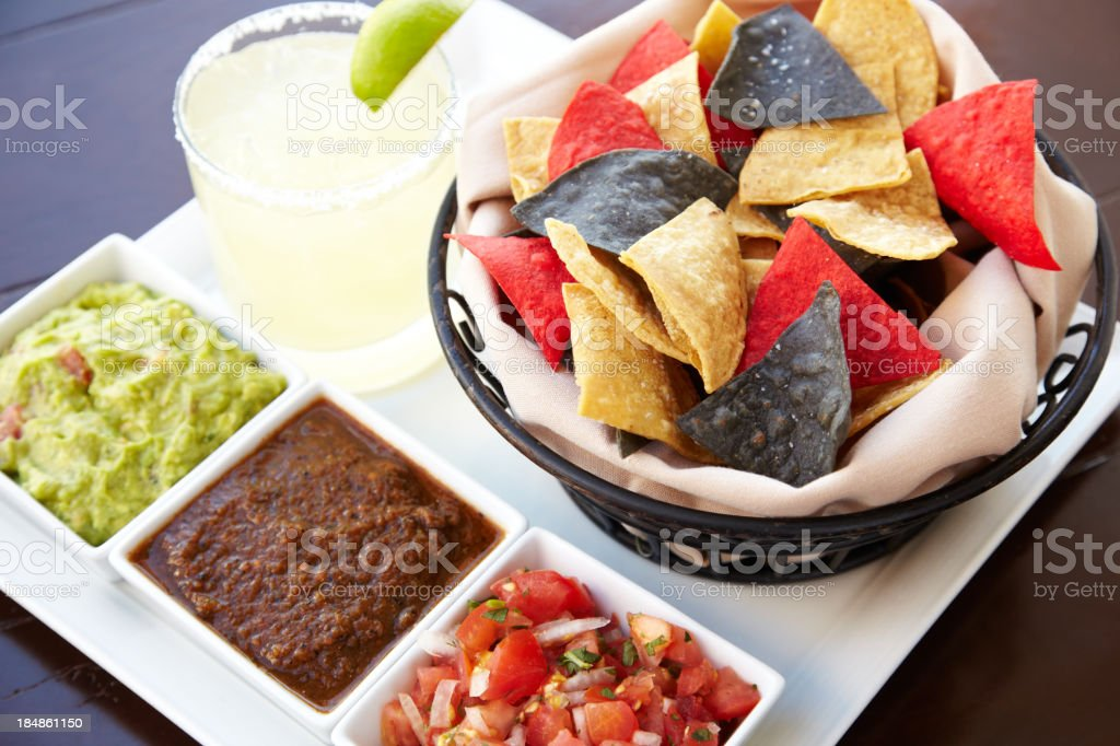 Bowls containing Nachos guacamole and tomato dip with margarita royalty-free stock photo