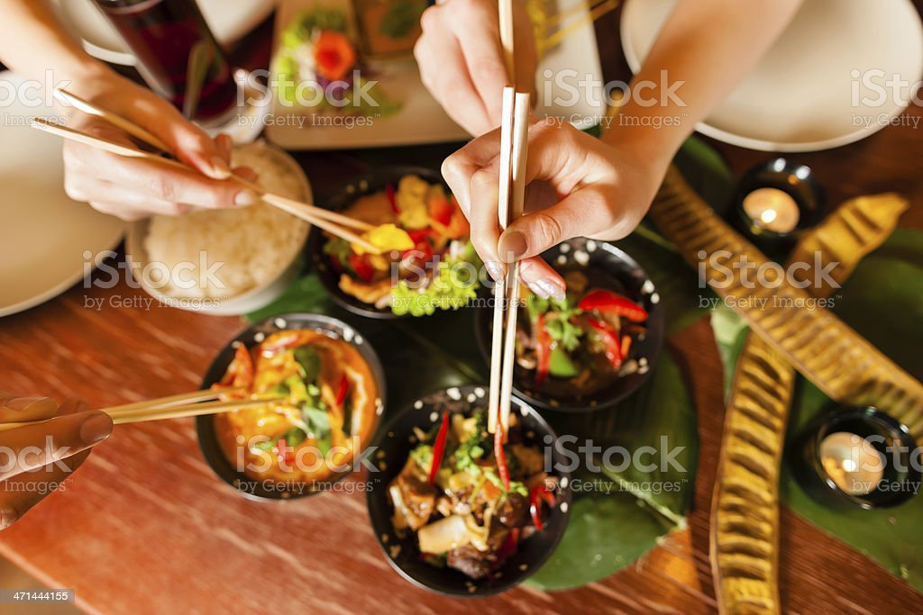 Bowls of food in Thai restaurant and hands using chopsticks stock photo