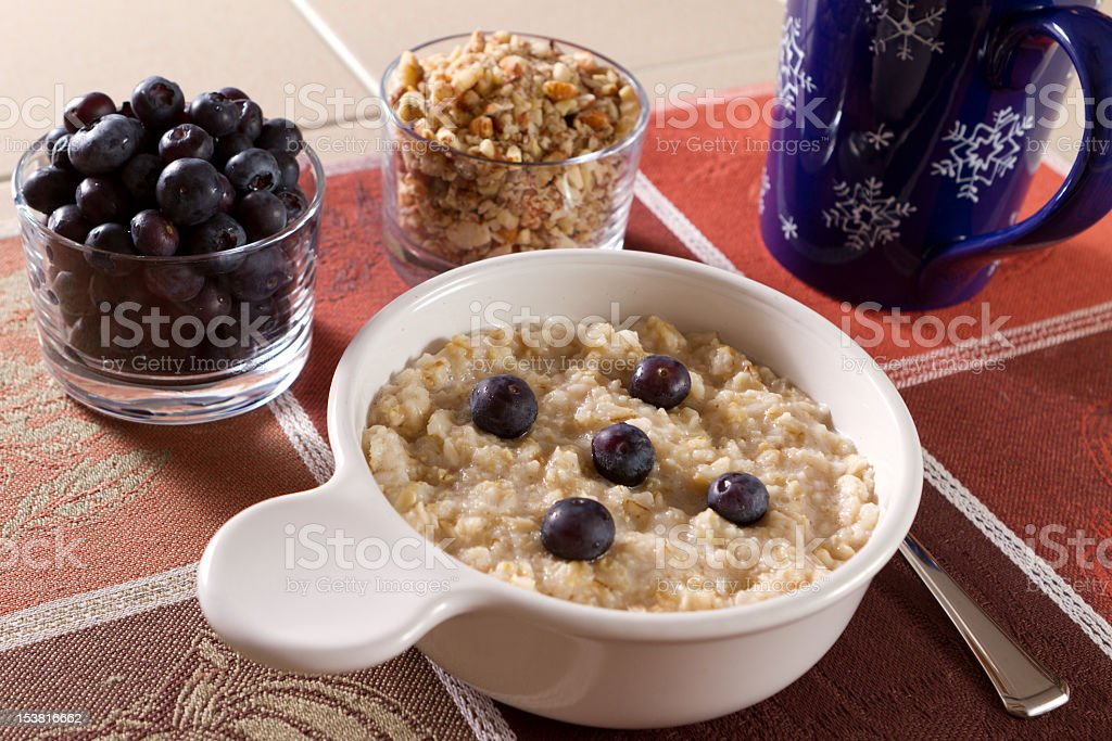 Bowls of hot oatmeal, blueberries, ground nutsfor breakfast. stock photo
