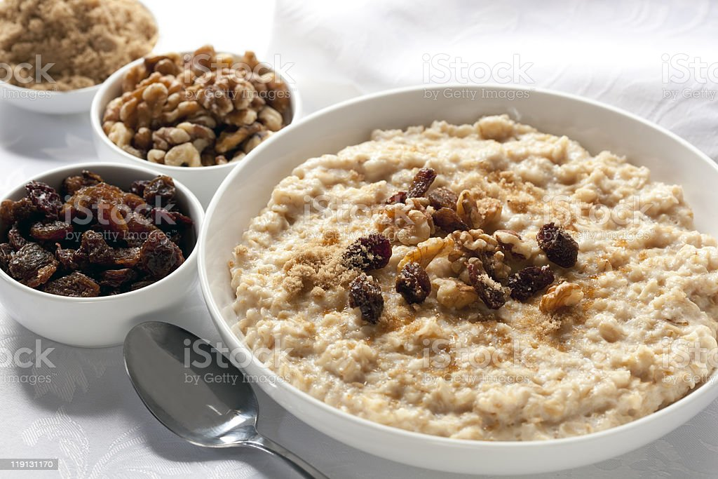 Bowls of oatmeal sitting on white detailed tablecloth stock photo