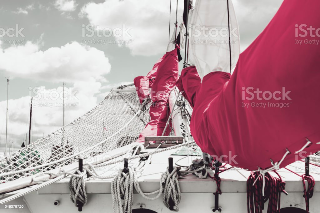 Bowsprit and gathered red sail of the sailing ship. stock photo