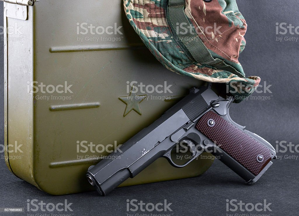 Box for bullets, a gun and a camouflaged hat stock photo