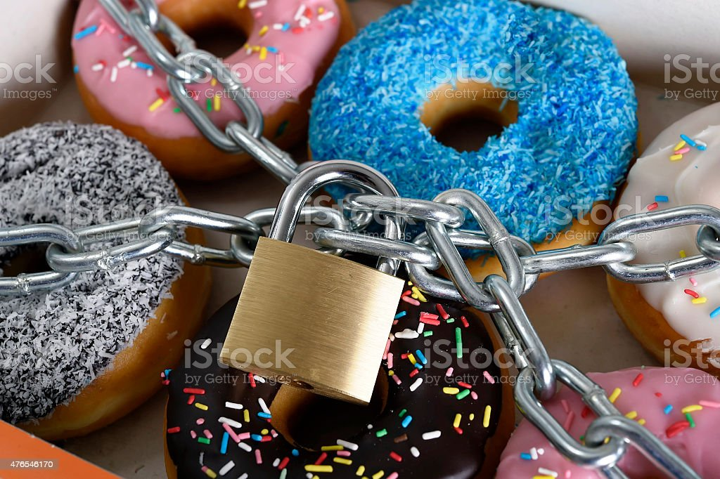 box full of donuts wrapped in metal chain and lock stock photo