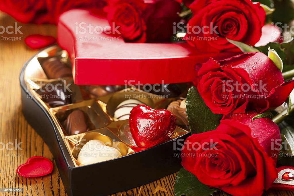 box of chocolate truffles with red roses stock photo