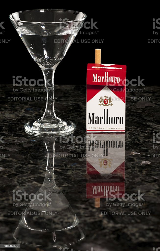 Box of Marlboro Red Cigarettes on Bar Top with Drink royalty-free stock photo