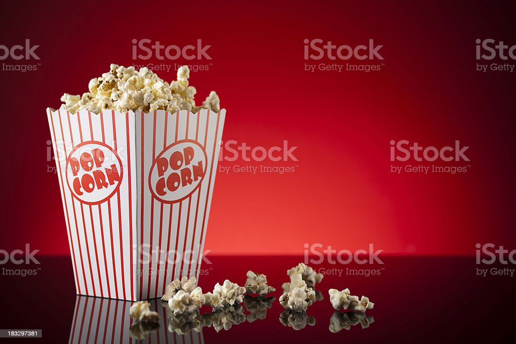 Box of popcorn on reflective surface and red background stock photo