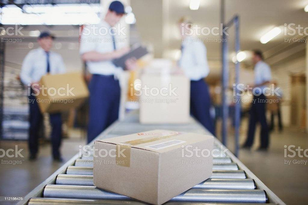 Box on conveyor belt in shipping area stock photo