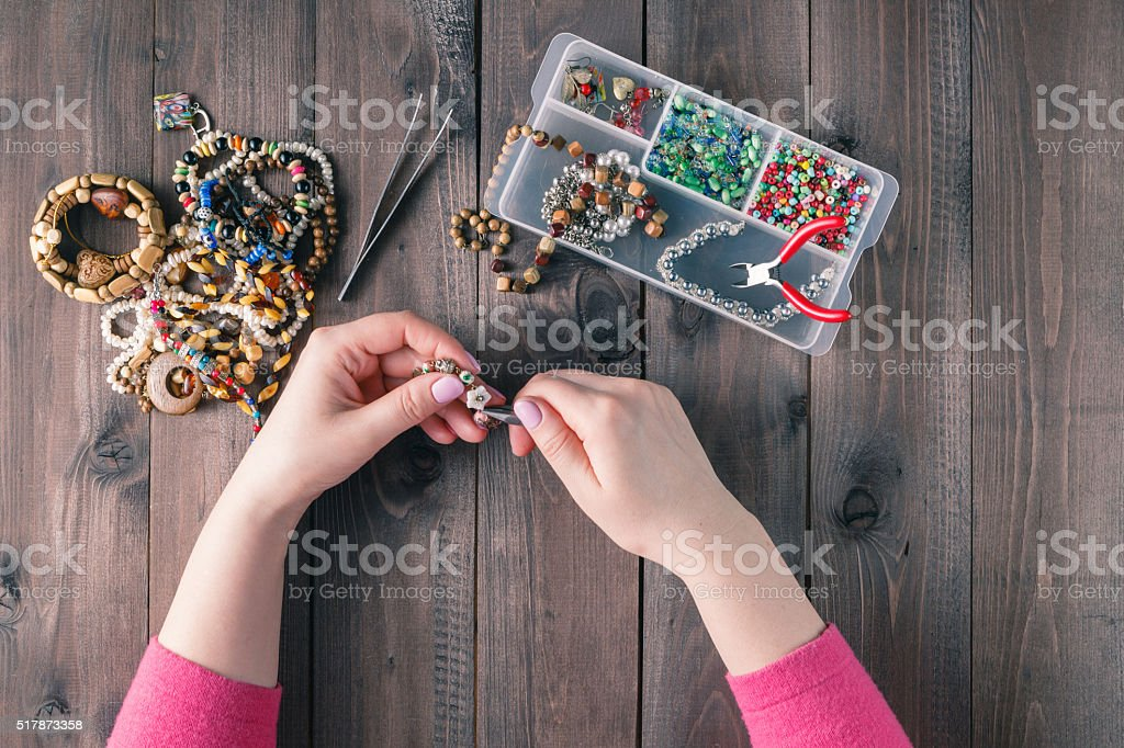 Box with beads on old wooden background. Handmade accessories stock photo