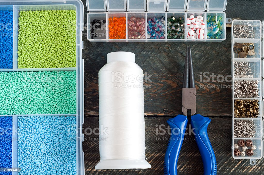 Box with beads, thread, pliers to create jewelry. Handmade accessories stock photo